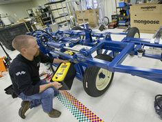 Bryon Majusiak installs the batteries on the tool bar of a lettuce-thinning robot at Blue River Technology in Sunnyvale, Calif. It is a sign of the booming activity surrounding the so-called ag-tech sector.