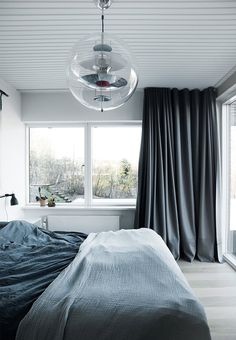 Sleep in a dark and cozy den - Heavy fabric curtains, the bright bedroom with many windows can be transformed into a dark and cozy den. The pendant Globe is designed by Verner Panton.