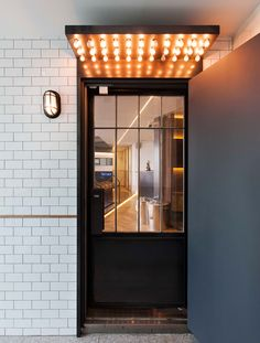 a ton of lighting bulbs above entry. shop window в 2019 г Facade Design, Door Design, Exterior Design, Interior And Exterior, Sign Design, Shop Front Design, Facade Architecture, Cafe Interior, Commercial Interiors