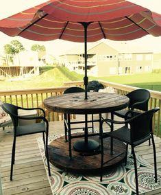 idee-amenagement-terrasse-surelevée-revetement-sol-en-teck-table-en-touret-et-un-parasol-qui-passe-au-centre-chaises-de-jardin-noirs-tapis-motifs-floraux