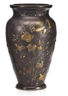 A patinated bronze vase with mixed-metal design Meiji period (late 19th century) The tapering ovoid body decorated in high relief with butterflies and a song bird amid flowering autumn plants and grasses, executed in gold, silver, copper and shakudo and with incised accents, further mixed metal overlay of floral tendrils applied to the waisted neck
