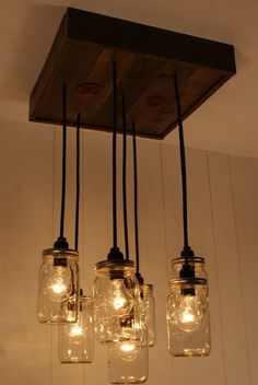 This unique Mason Jar light pendant chandelier is meticulously handcrafted using reclaimed wood. We are woodworkers by trade and we take pride in our materials and craftsmanship. Each piece of wood is inspected and hand selected for each fixture we c Mason Jar Chandelier, Mason Jar Lighting, Pendant Chandelier, Kitchen Lighting, Light Pendant, Chandelier Ideas, Bottle Chandelier, Mason Jar Crafts, Mason Jar Lamp