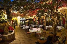 Mission Inn, Riverside CA.  This outdoor courtyard is perfect at night for a romantic dinner.  I love the lights in the trees and the open fireplaces and firepits by the tables.