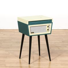 "This ""Crosley"" mid century modern style record player is featured in a black, teal blue and off white plastic. This newer record player has tall slanted tapered leg with a lift up top and record player with a speaker base. Great for a retro room! #americantraditional #decor #accents #sandiegovintage #vintagefurniture"