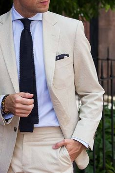 Summer seersucker suit in cream with navy knit tie and pocket square