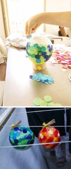 Hemos pegado confetti enorme en un globo con cola de empapelar.Y para que se sequen estan colgados en el tenderero. En elpróximopost va...