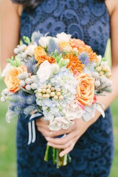 blue and orange bouquet featuring roses, hydrangeas, thistle and silver brunia by Kim John Designs