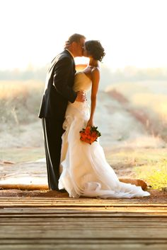 deep kiss with her hand closest to camera holding bouquet hanging down and his at waist line...