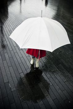 White umbrella and boots...black planks...red raincoat
