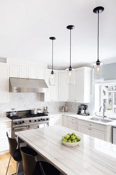 FH added a custom island accented with white macaubas quartzite, quartz perimeter countertops, a marble herringbone backsplash, wide planked oak flooring and Hennepin Made pendants. #islandpendantlights