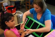 A teacher uses speech and tactile signing to prompt a student to find the appropriate tangible symbol card.