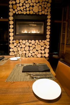 double fire place covered on all sides in log ends