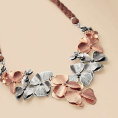 Braided leather and a garland of flowers, with rose and silver-tone accents, create this unique piece.