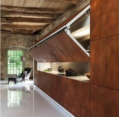 Contemporary kitchen design with folding front panels hides a cooktop and storage shelves when you do not use them. Hidden Kitchen design from Warendorf shows a new kitchen concept that is attractive,