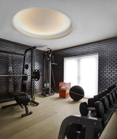 A beautiful home gym with light wood floors and black brick walls give a calming, zen look