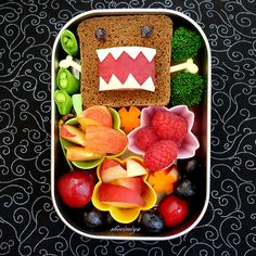 Monster Bento – Cream cheese sandwich using rye cocktail bread, which is square-shaped & comes in a long loaf. His eyes are bits of grapes, his mouth is a red plum, & his teeth are cut from mozzarella. A few little cups of fruit: peach, nectarine & raspberries, along with cherries & grapes. A few peapods, carved carrots & tiny broccoli florets.