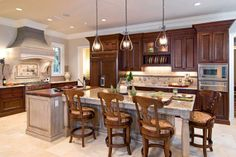 Located next to the range, the working end of this kitchen island is capped with a thick wooden counter made of aged walnut and a small prep sink. Three Hubbardton Forge pendants illuminate the seating portion of the island, which features a light finish that contrasts the dark perimeter cabinetry.