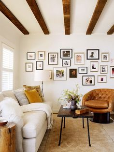 Cozy living room with white couch, leather armchair, and gallery wall