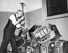 In this photo that ran in the Dec. 28, 1940, edition of The World-Herald, Sheriff W.H. Dorrance takes a sledgehammer to confiscated slot machines and other gambling devices, following an order from District Judge Willis G. Sears. Nearly $200 in nickels, dimes and pennies was removed from the machines, which were seized by authorities earlier in the year. The money was delivered to the county treasurer's office. THE WORLD-HERALD