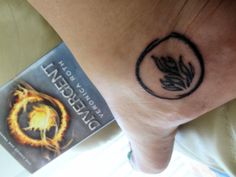 "The symbol is inspired by Divergent (by Veronica Roth), and it represents the Dauntless, one of five factions of government in a dystopian Chicago. The Dauntless motto: 'We believe in ordinary acts of bravery, in the courage that drives one person to stand up for another.'"" maybe my book tattoo??"