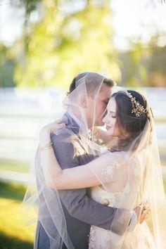 The groom kisses the bride on the cheek beneath her delicate veil. #WeddingVeil #WeddingCouple Photography: Amanda McKinnon Photography. Read More:  http://www.insideweddings.com/weddings/bride-wears-claire-pettibone-gown-to-bohemian-outdoor-wedding/668/