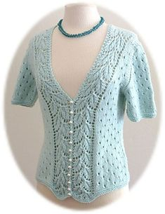 """This is a top with V-neckline and short set-in sleeves. The top is open in front and has the same lovely """"Drooping Elm Leaf"""" pattern on both sides of the front opening. The rest of the body follows an easy eyelet pattern. Decreases are done at the outside edge of the leaf pattern. As a result, the leaf pattern is not interrupted. Pearl buttons finish the front."""