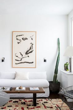 Minimal white living room with cactus in New York City apartment tour on Thou Swell @thouswellblog