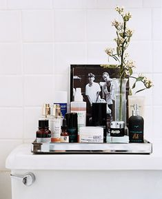 "Realize the Power of Trays  Instead of crowding your sink with creams, put your products on display. Korban creates a back-of-toilet tableau by grouping his on Venetian glass, arranging jars up front and tall bottles in the rear for easy access—and decorates them with a framed photo and fresh flowers.    (Similar to shown) ""Can Can Girl"" mirror tray $34 urbanoutfitters.com"