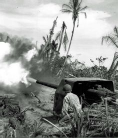 American soldiers are firing from a captured Japanese gun