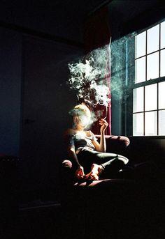 Smoking, a shaft of sunlight.