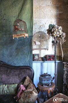 Anciennes cages à oiseaux abritant des figurines en papier, suspendues dans le salon de Miss Clara