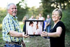 Parents holding their wedding photo with their family in the background, cute idea for an anniversary