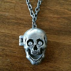 "Disney's ""Pirates of the Caribbean"" Skull Locket Distressed silver tone. Magnetic skull with rhinestone eyes. Jack Sparrow/Johnny Depp photo inside and authentic Disney stamp on the outside. It measures between 20-22"". Disney Jewelry Necklaces"