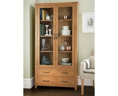 Display all sorts of household items in traditional style with this great-looking cabinet. Solidly built and expertly crafted in solid oak with veneer panelling,