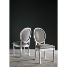 Brimming with French country charm, this set of two dining chairs boasts a classic cream frame, light grey linen upholstery and Provencal-style oval back.
