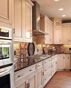 Light cabinets, dark counter, oak floors, neutral tile black splash.