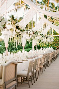 Cascading drapes, delicate chandeliers, and suspended bouquets of blooms and greens are nothing but chic.