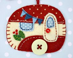 Vintage caravan trailer hanging ornament, handmade from felt and decorated with fabric scraps. With tiny felt bunting and buttons for the wheel
