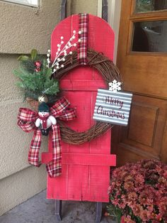 Pallet sled embellished with wreath. It's perfect for a front porch for Christmas.