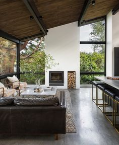 A 1957 Midcentury in Seattle Receives a Striking Makeover - Photo 5 of 12 - A new double-height fireplace is now the focal point of the spacious living room. It effortlessly underscores the room's graceful proportions.