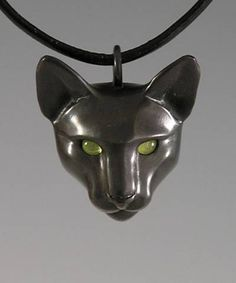Black Cat w/ Peridot Eyes/ Center Bail, on leather cord   .  Cast bronze w/ black patina, Peridot eyes, leather cord w/ lobster clasp at back.  Cat head: 1 1/4 inch X 1 1/4 inch.  $ 200.00