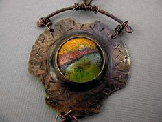 Cut and distressed brass disc with no solder bezel. Dapped bronze coin with torch-fired enamel by Vintajia Adornments