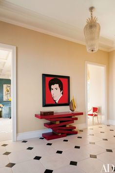 In the foyer, a 1983 Andy Warhol portrait of Wynn surmounts a Van der Straeten console from Ralph Pucci International; the ceiling light is from Bernd Goeckler Antiques. | archdigest.com