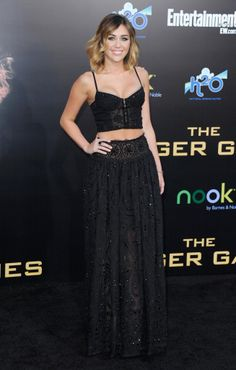 Miley Cyrus in an Emilio Pucci black mesh beaded bustier with a black high-waisted organza skirt with beaded applique from the Spring Summer 2012 collection to the Hunger Games Premiere at the Nokia Theatre L.A. LIVE in Los Angeles.