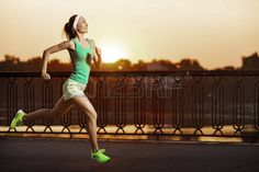 Running woman. Runner is jogging on sunrise. Female fitness model training outside in the city on a quay. Sport lifestyle. photo
