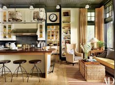 At a retreat in the Adirondacks, the kitchen cabinetry, designed by decorator Thom Filicia and architecture firm Shope Reno Wharton, is painted in a Farrow & Ball white. The hood is by Wolf, the backsplash tile is by Urban Archaeology, the sink fittings are by Waterworks, and the barstools are by Marsia Holzer Studio. The wing chair, from Lillian August, and the Thom Filicia Home Collection sofa are upholstered in Perennials fabrics, and the rug is by Stark.