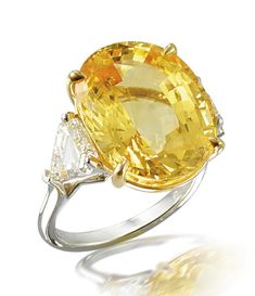 A yellow sapphire and diamond ring The oval mixed-cut yellow sapphire, flanked by triangular-cut diamonds, mounted in platinum and 18k gold, yellow sapphire approximately 20.55 carats, diamonds approximately 2.55 carats total,