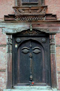 Buddha's Eyes on Nepalese Wooden Door, Durbar Square area of Bhaktapur, Nepal *