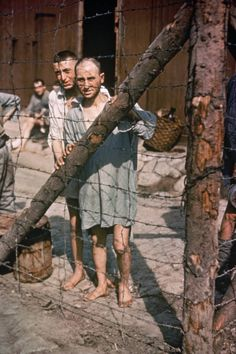 Two World War II prisoners of war stare through a barbed wire fence at Buchenwald Concentration Camp near Weimar, Germany in Pin by Paolo Marzioli World History, World War Ii, Buchenwald Concentration Camp, History Magazine, Life Magazine, Prisoners Of War, Wwii, The Past, Images