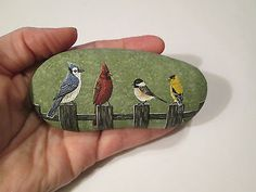 Cardinal-Bluejay-Chickadee-Goldfinch-hand-painted-on-a-rock-by-Ann-Kelly